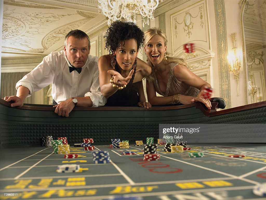 Woman throwing dice at craps table in casino, friends watching