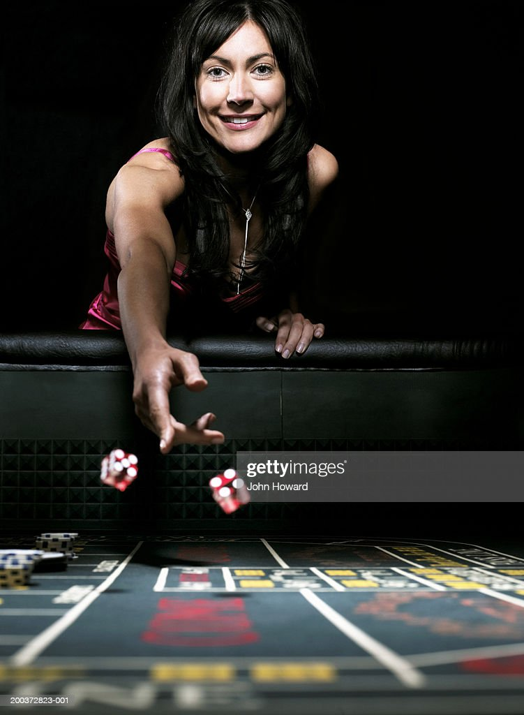 Woman throwing dice on gaming table, smiling, portrait