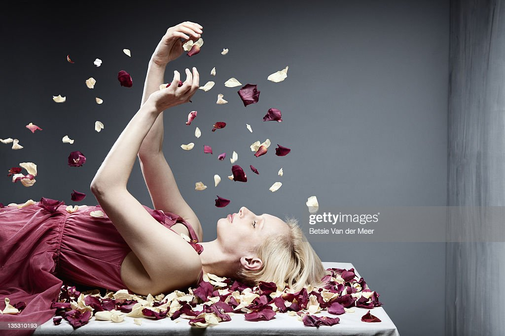 Woman throwing flowerpedals up in air. : Stock Photo