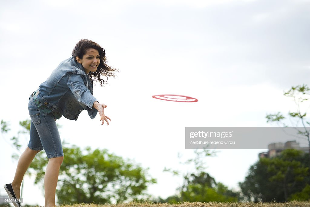 Woman throwing flying disc at park