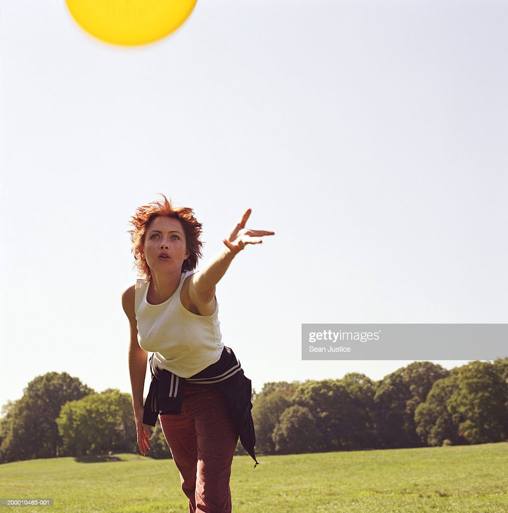 Woman throwing flying disc in park