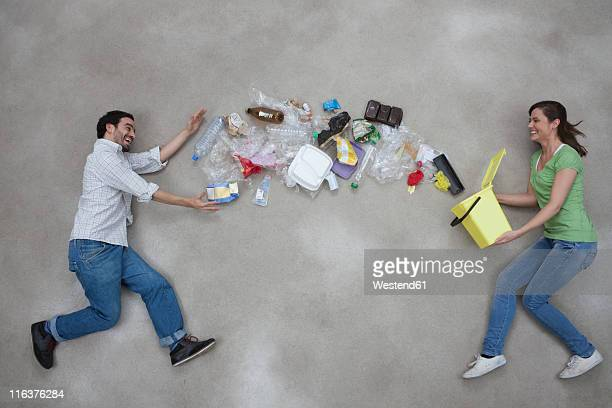 Woman throwing garbage towards man