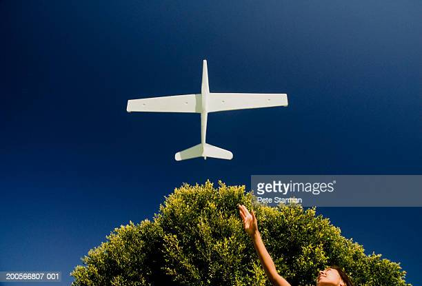 Woman throwing glider into air, low angle view