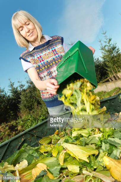 Woman throwing kitchen waste into a compost bin