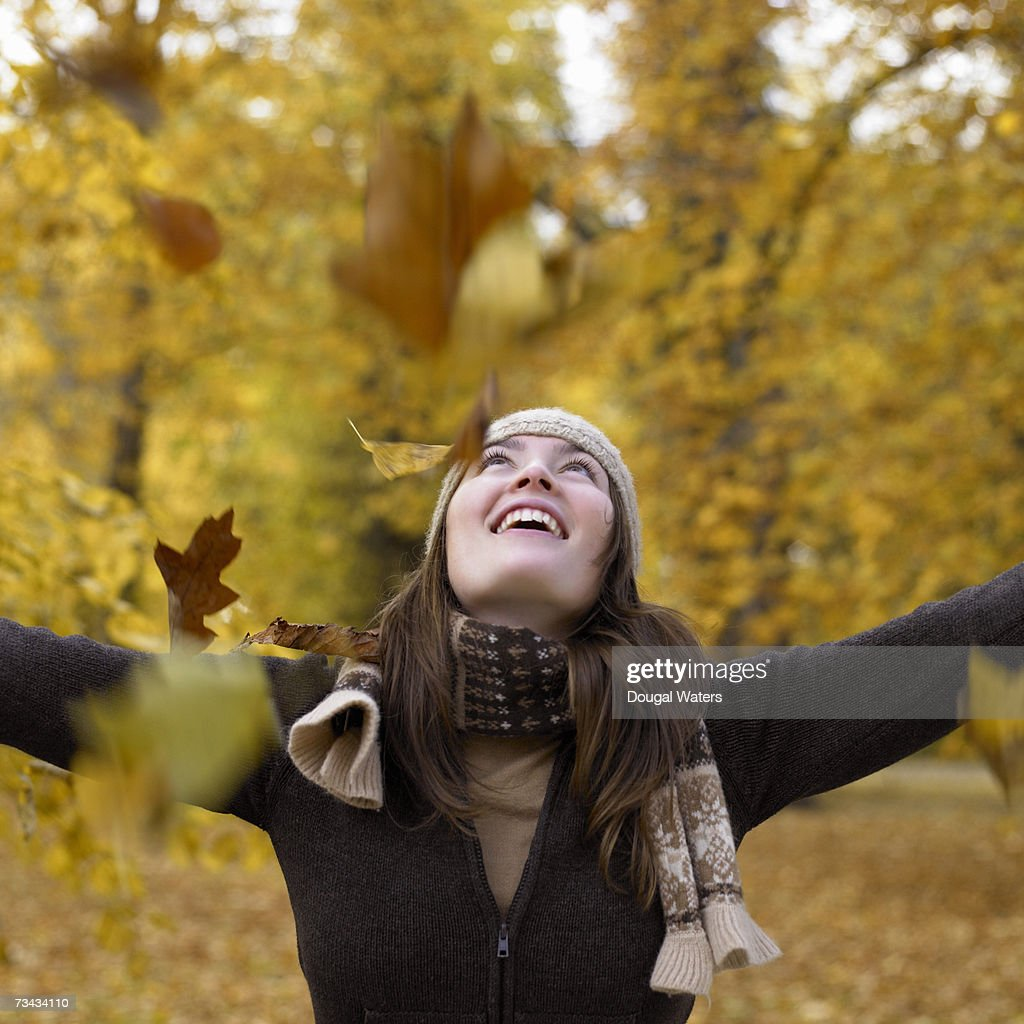 Woman throwing leaves in autumn forest : Stock Photo