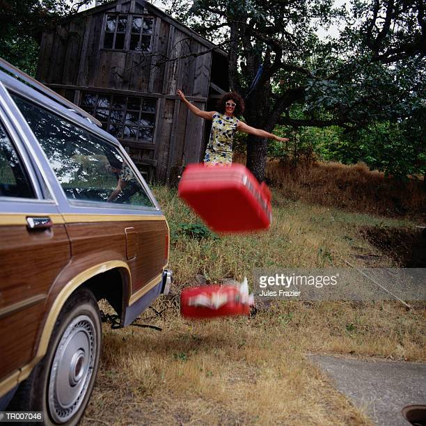 Woman Throwing Luggage to Car