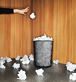 Woman throwing paper in waste paper bin, close-up of hand