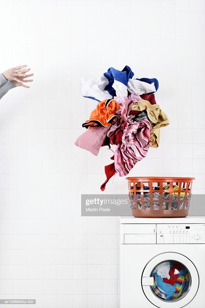Woman throwing pile of laundry to basket on washing machine : Stock Photo