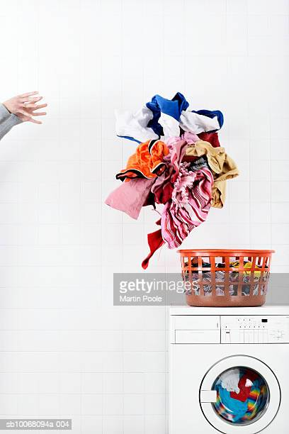 Woman throwing pile of laundry to basket on washing machine