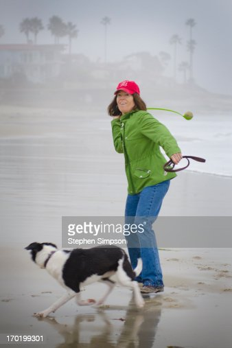 woman throwing tennis ball on the beach for her do : Foto de stock