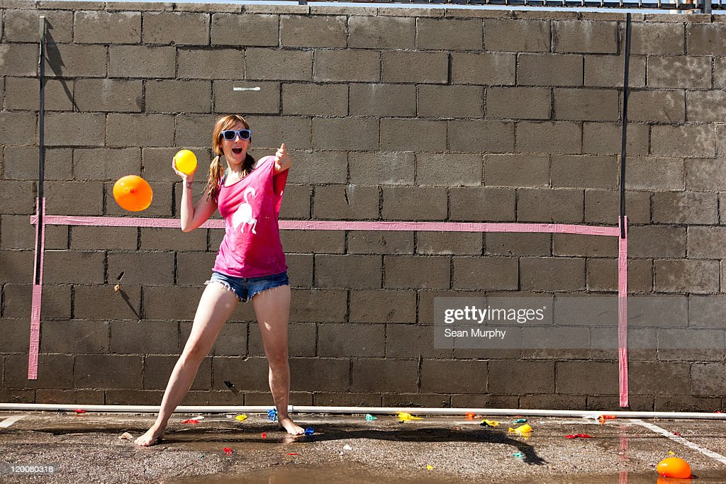 Woman throwing water balloon, concrete wall behind