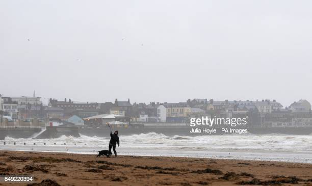 A woman throws a ball for her dog in the wind and rain on South Beach in Bridlington East Yorkshire