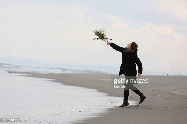 A woman throws a flower bunch at Fukanuma beach on March 11 2016 in Sendai Japan Today marks the fifth anniversary of the magnitude 90 earthquake and...