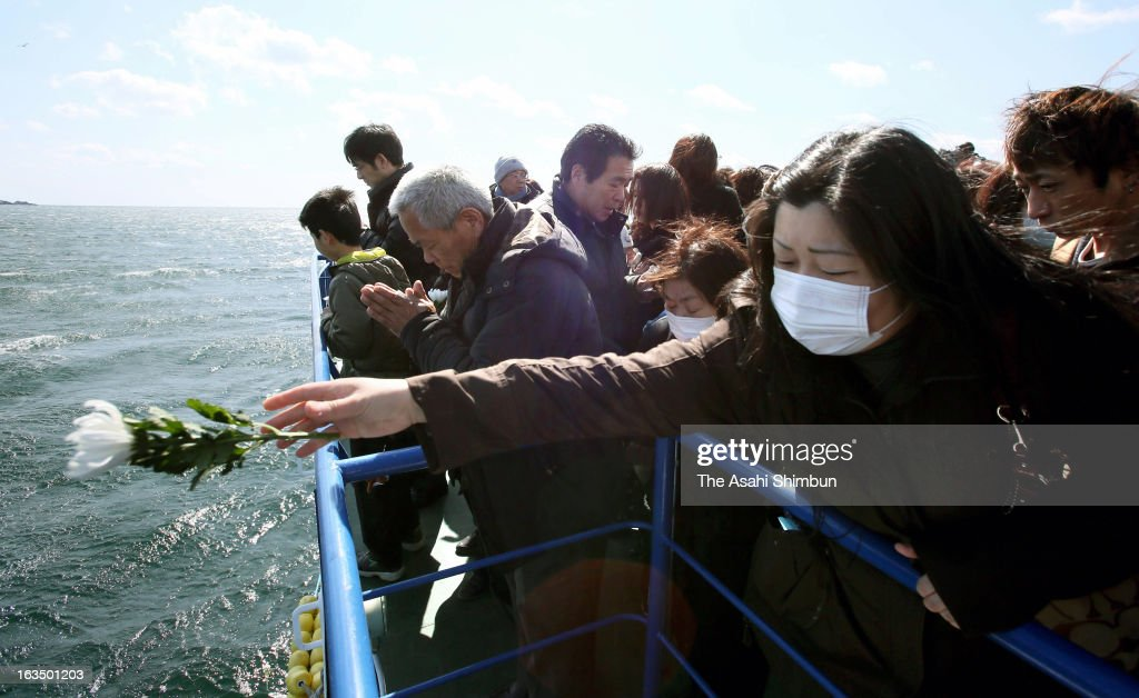 A woman throws a flower into the sea, during the memorial service on March 11, 2013 in Kesennuma, Miyagi, Japan. On March 11, Japan marks second anniversary of the Magnitude 9.0 earthquake and subsequent tsunami, that claimed more than 18,000 lives.