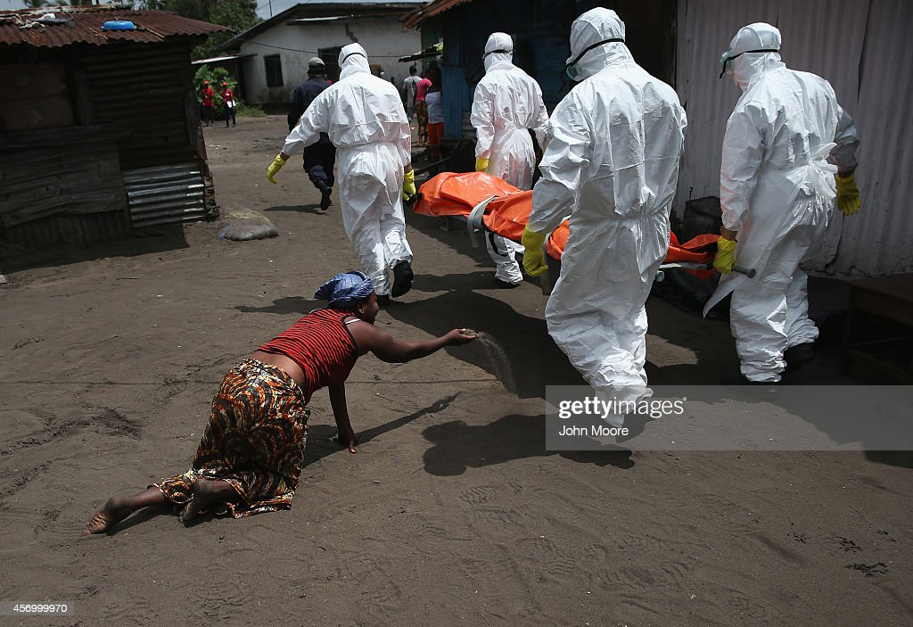 A woman throws a handful of soil towards the body of her sister as Ebola burial team members take her sister Mekie Nagbe for cremation on October 10...