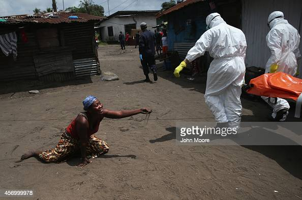 A woman throws a handful of soil towards the body of her sister as Ebola burial team members take her Mekie Nagbe for cremation on October 10 2014 in...