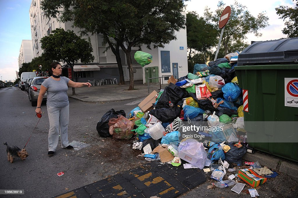A woman throws a plastic bin onto a garbage heap during the 21st day of the garbage collectors strike on November 22, 2012 in Jerez de la Frontera, Spain. The garbage collectors will vote later today on a compromise deal which saves the 123 jobs due to be cut in favour of reductions in saleries.