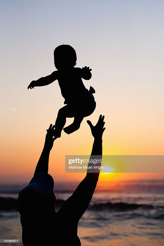 A woman throws her baby into the air. : Stock Photo