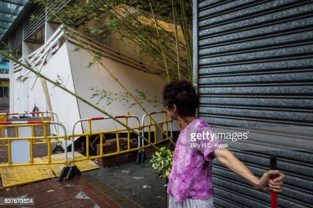 A woman tidies the street as typhoon Hato hits Hong Kong on August 23 2017 in Hong Kong Hong Kong Hong Kong's weather authorities raised Typhoon Hato...