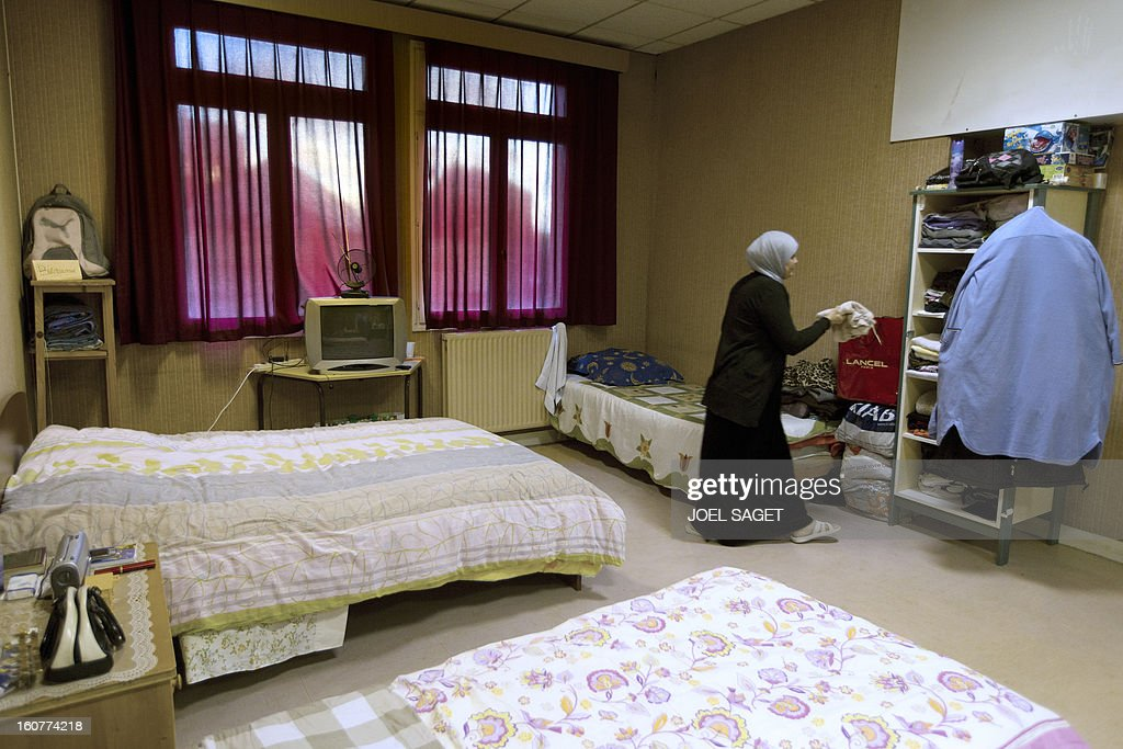 A woman tidies up her things in an emergency shelter for homeless families administered by Catholic parishes on February 5, 2013 in Neuilly-sur-Marne, outside Paris.