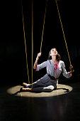 Woman tied in strings sitting on floor with spotlight
