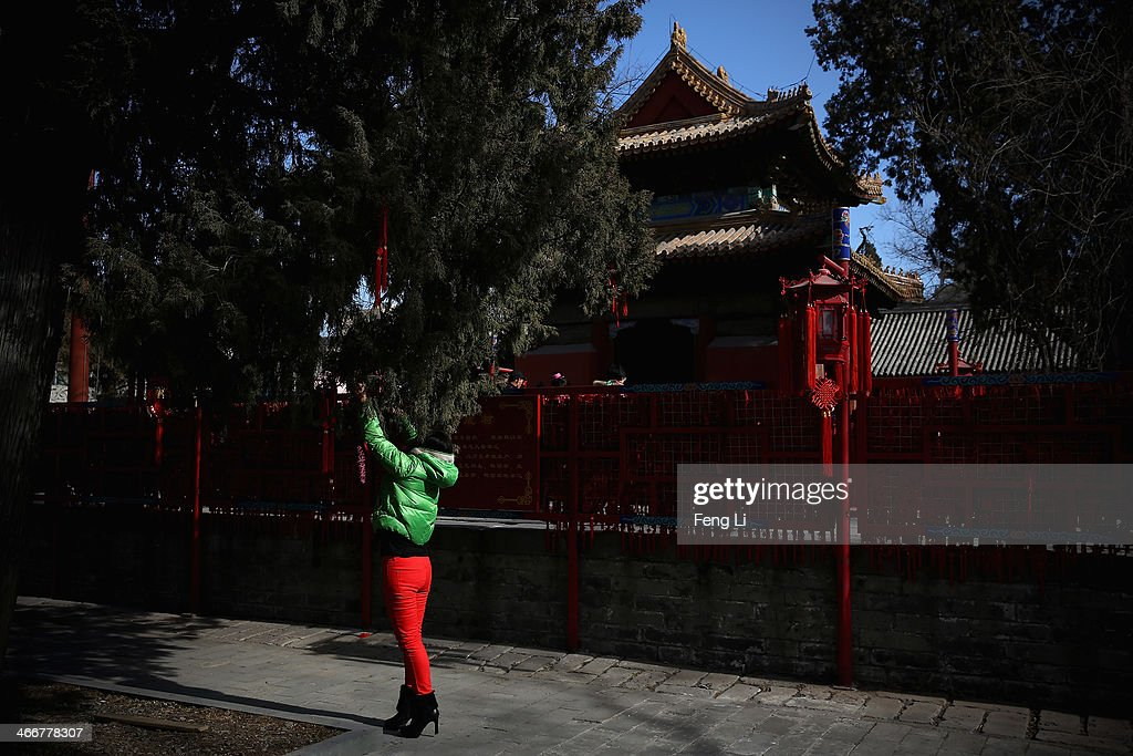 A woman ties new year wishes on a tree during a Spring Festival temple fair on the fifth day of the Chinese Lunar New Year of Horse on February 4, 2014 in Beijing, China. The Chinese Lunar New Year of Horse also known as the Spring Festival, which is based on the Lunisolar Chinese calendar, is celebrated from the first day of the first month of the lunar year and ends with Lantern Festival on the Fifteenth day.