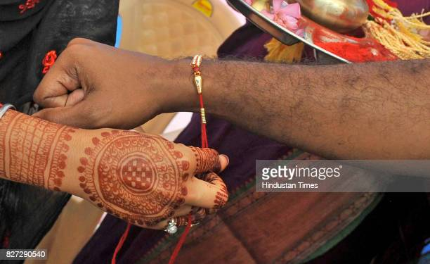 A woman ties rakhi on the wrist of a paramilitary officer of Central Reserve Police Force during an event to celebrate the Raksha Bandhan festival at...