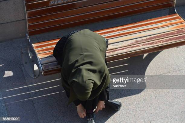 A woman ties shoe laces in the historic Ulus district of Ankara Turkey on October 20 2017