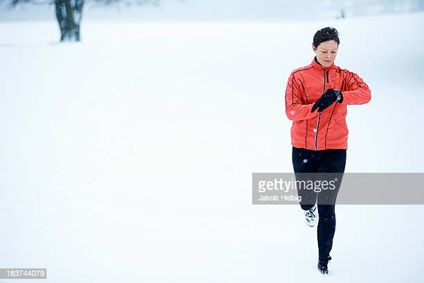 Woman timing her snow running