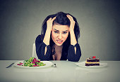 Woman tired of diet restrictions deciding whether to eat healthy food or sweet cake dessert she is craving isolated grey background. Human face expression emotion.