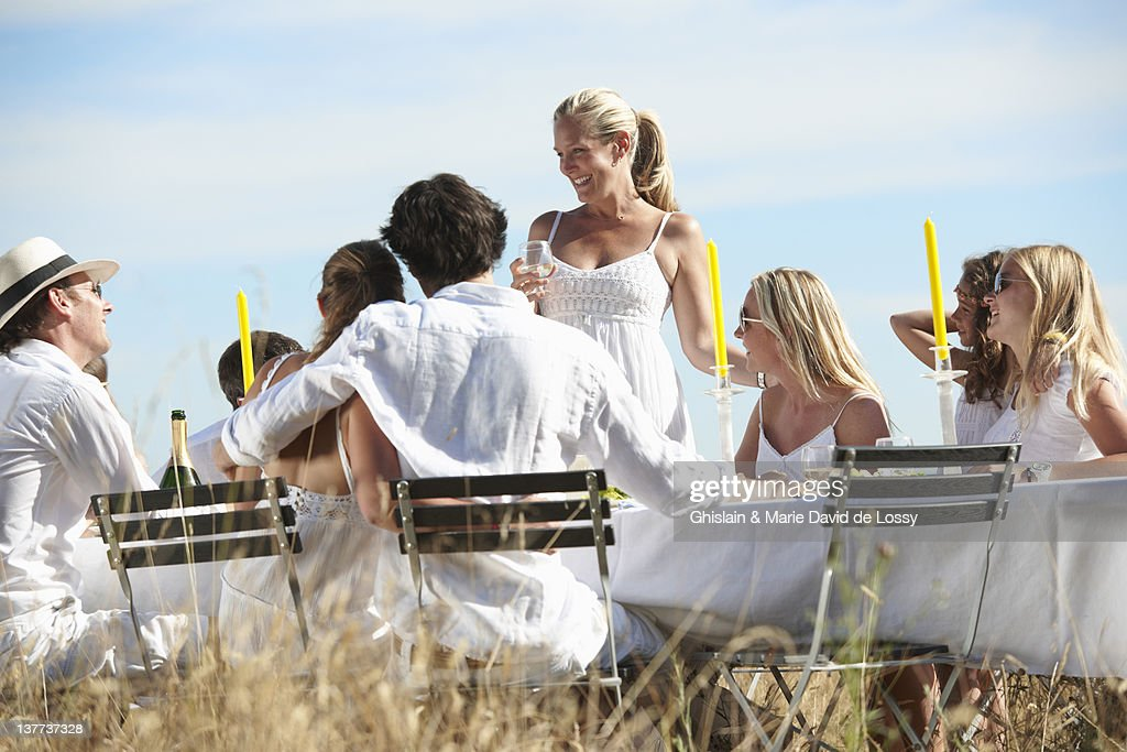 Woman toasting at table outdoors : Stock Photo