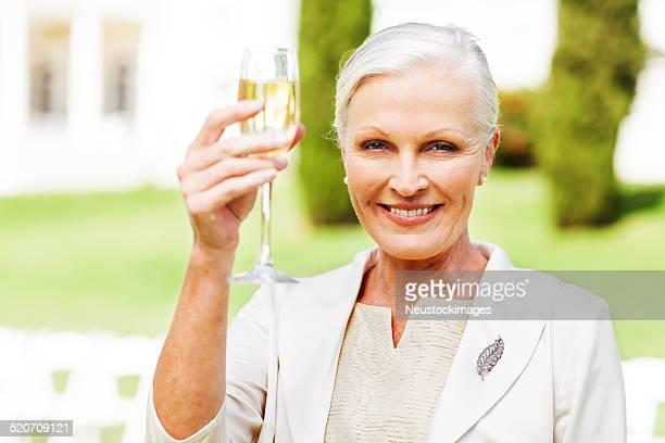 Mulher de tostar Champagne no casamento ao ar livre