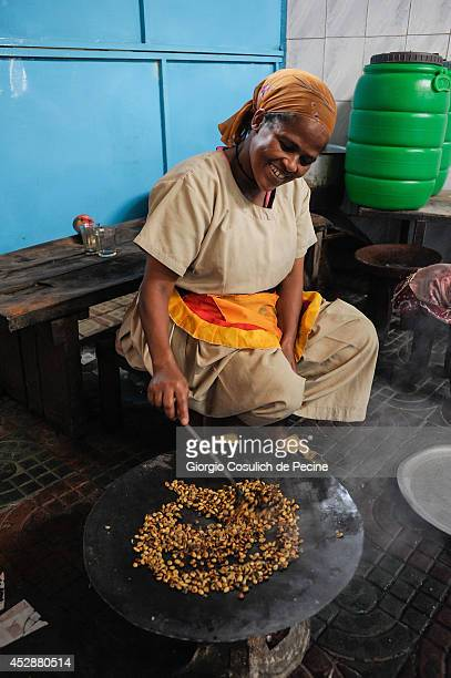 A woman toasts coffee beans on July 01 2014 in Addis Ababa Ethiopia The Ethiopian government has recently launched a new urban plan for the...
