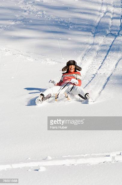 Young woman tobogganing in snow, smiling