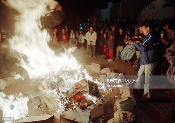 A woman tosses a Ouija Board into a bonfire outside the Christ Community Church December 30 2001 in Alamogordo New Mexico The churchs pastor urged...