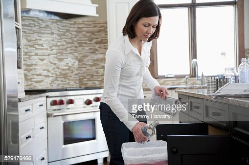 Woman tossing an empty bottle away : Stock-Foto