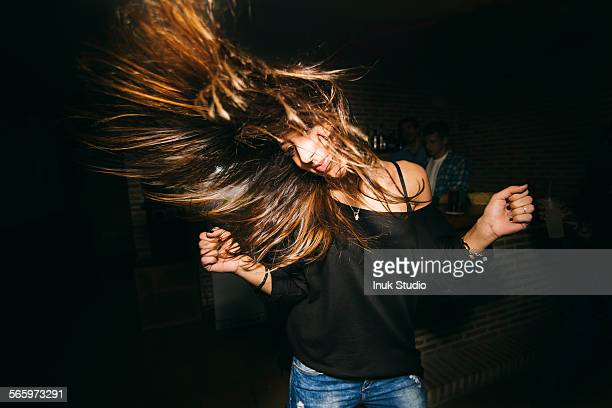 Woman tossing her hair and dancing in nightclub