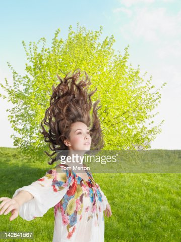 Woman tossing her hair in rural field : Stock Photo