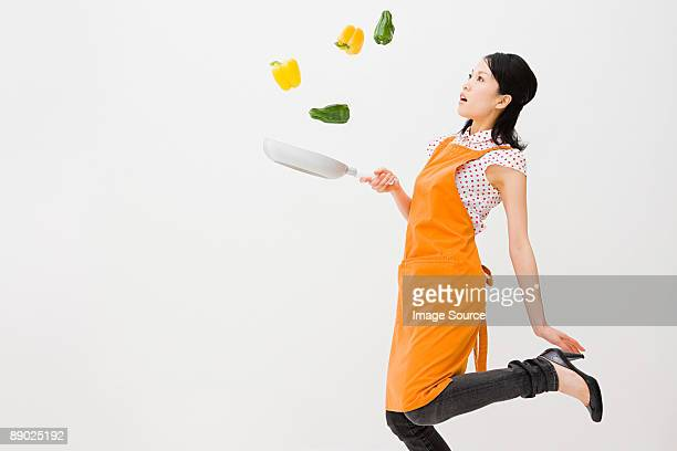 Woman tossing peppers