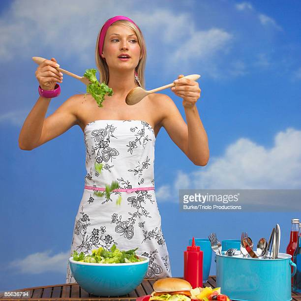 Woman tossing salad at barbeque