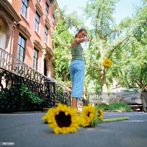 Woman tossing sunflowers to the ground