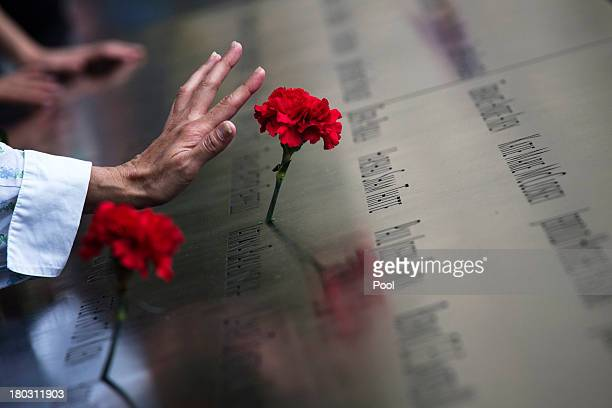 A woman touches a carnation left on a name inscribed into the North Pool during 9/11 Memorial ceremonies marking the 12th anniversary of the 9/11...