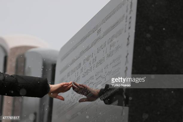 A woman touches a memorial engraved with the names of the victims at Okawa Elementary School on the three year anniversary of the earthquake and...