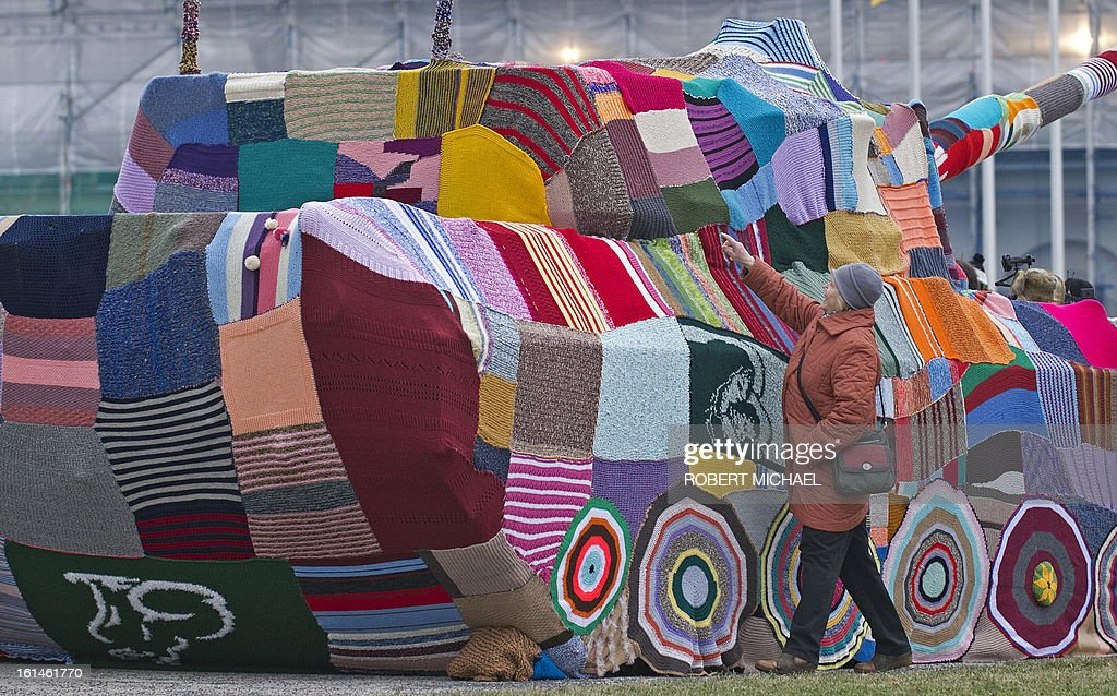 A woman touches a piece of knitted fabric covering a tank wich stands in front of the Museum of Military History in Dresden, eastern Germany, on February 11, 2013. The Leopard I tank takes a stand with a cross-generational handicrafts project against war and violence on the occasion of 68th anniversary of the bombing of Dresden. AFP PHOTO / ROBERT MICHAEL