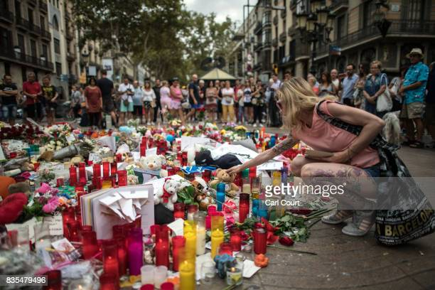 A woman touches a teddy bear that was placed with other tributes on Las Ramblas near the scene of Thursday's terrorist attack on August 19 2017 in...