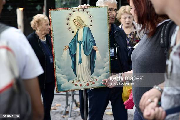 A woman touches an icon of the Virgin Mary in the Catholic pilgrimage city of Lourdes southwestern France on August 24 2014 AFP PHOTO / REMY GABALDA