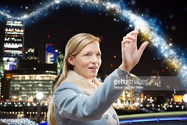 Woman touches energy light trail in city.