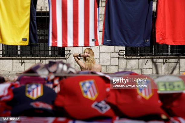 A woman touches her hair behind a merchandaising stall before the La Liga match between Club Atletico de Madrid and Sevilla FC at Vicente Calderon...
