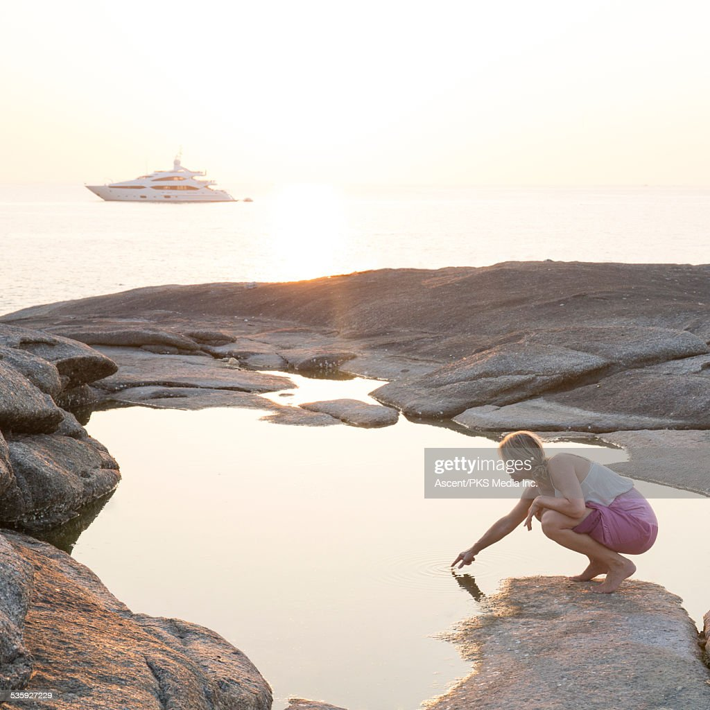 Woman touches surface of pool, boat & sea behind : Stock Photo