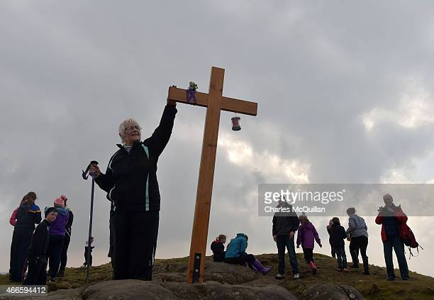 A woman touches the cross situated where St Patrick used to sit on a rock tending sheep as hundreds of people make the St Patrick's Day pilgrimage to...